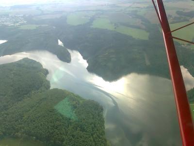 Kouzla světel a pohyby vody na jezeře, které z výšky vypadá jako větší rybník.